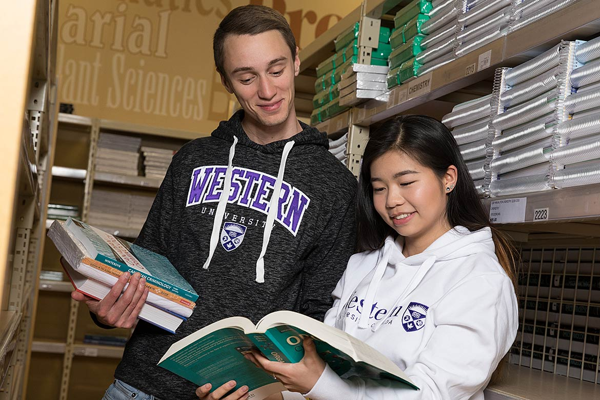 two students looking at textbooks