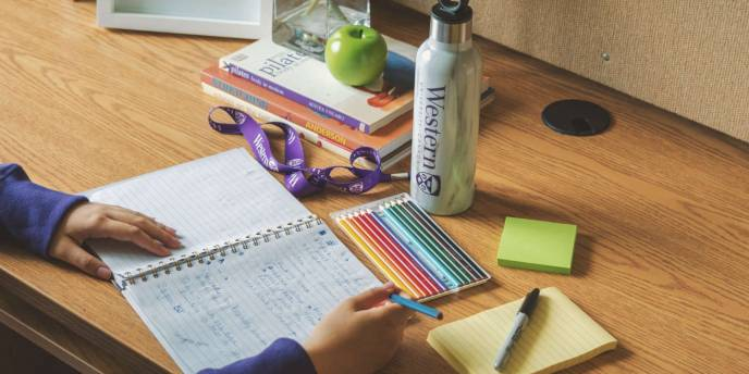a student taking notes at a desk covered in school supplies